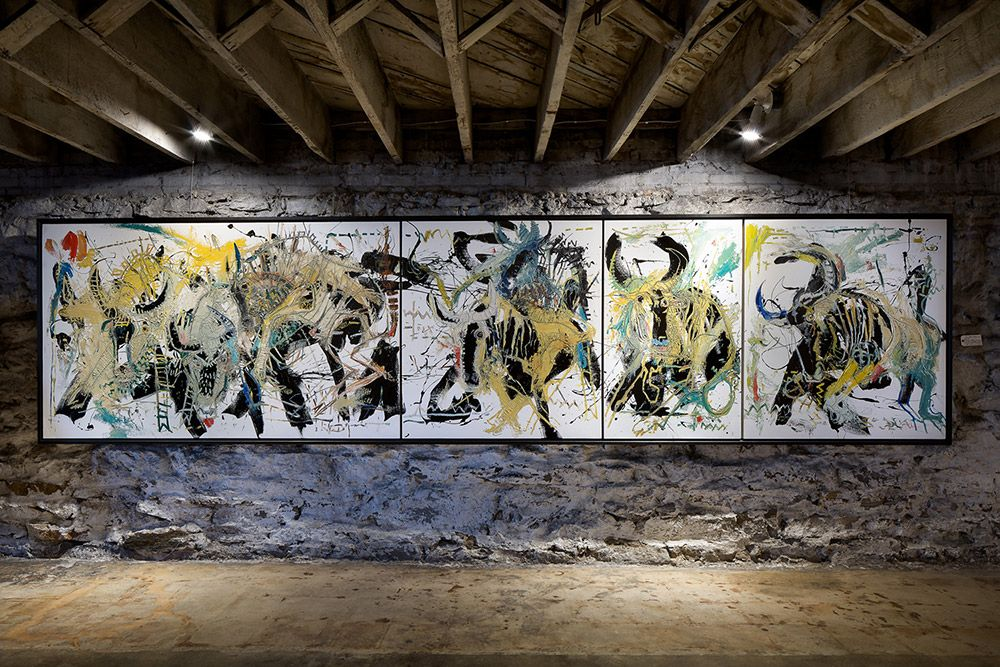 Large quadriptych painting titled Herd hangs on brick wall