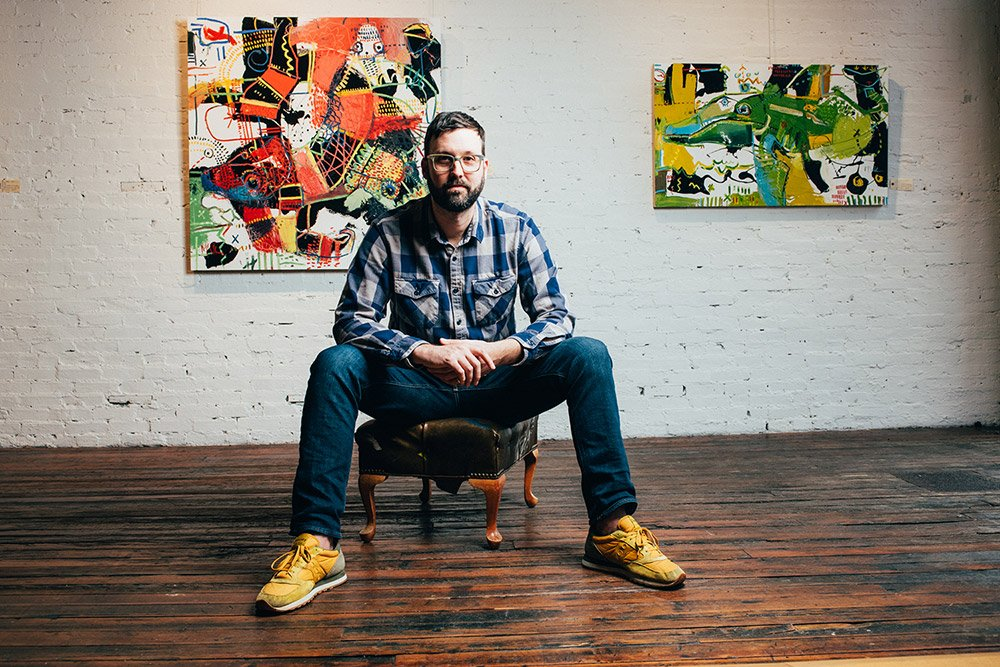 Daniel McClendon sits in his studio with his paintings behind him