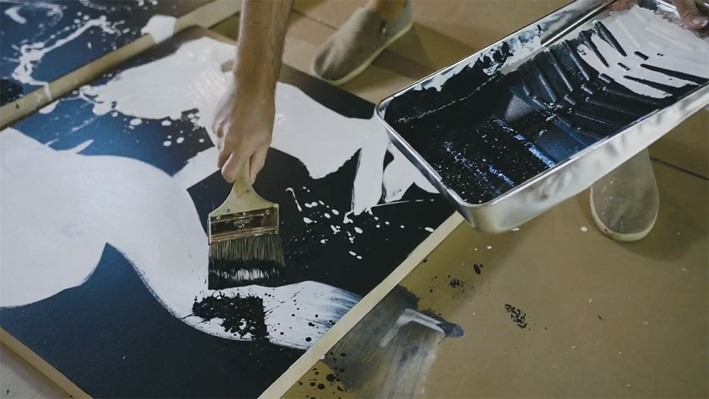 A paint brush splashes black paint on a black and white panel